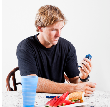 Young man checking his glucose with a CGM device after a meal.