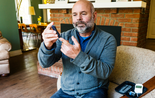 Man testing his glucose with a finger prick device